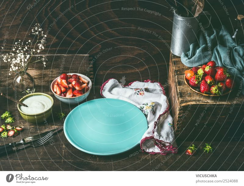 Empty blue plate on dark rustic wooden kitchen table with strawberries and yogurt in bowls. Country style food background with berries , still life. Place for your design, recipes , text or products