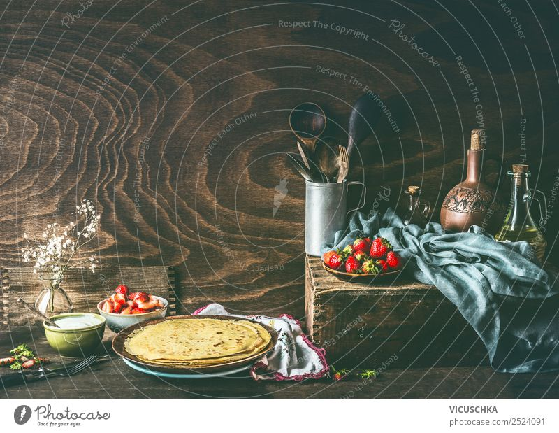 Country still life with homemade crepes on dark rustic wooden kitchen table with strawberries and yogurt in bowls . country strawberry top view cream fresh