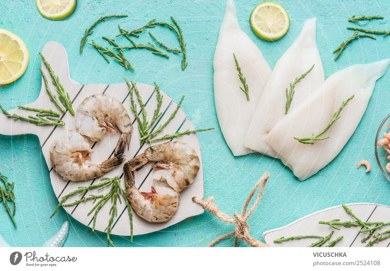 Raw prawn or shrimps and squids on light blue background, decorated with with seaweeds and lemon, top view, flat lay. Seafood cooking concept seafood above over