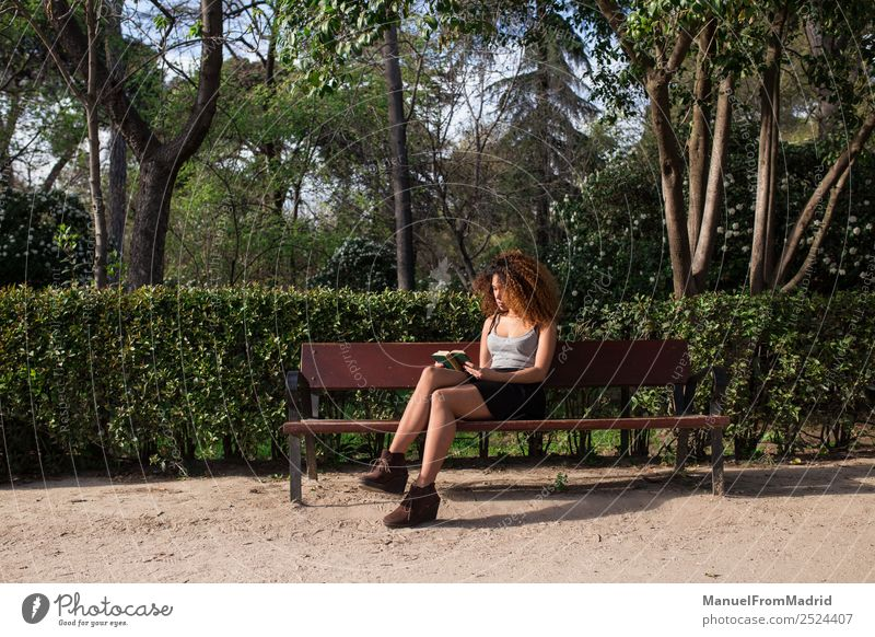 afro woman reading a book on a bench Lifestyle Happy Beautiful Leisure and hobbies Reading Summer School Study Human being Woman Adults Book Nature Tree Grass