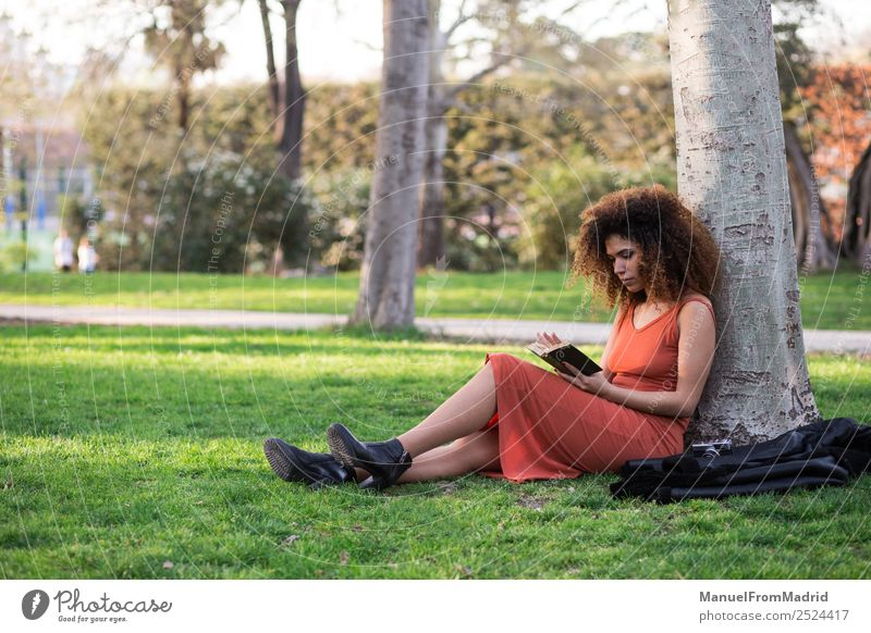 afro woman reading a book outdoors Lifestyle Happy Beautiful Leisure and hobbies Reading Summer School Study Human being Woman Adults Book Nature Tree Grass