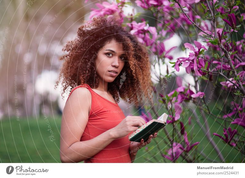 smart afro woman holding a book Lifestyle Happy Beautiful Leisure and hobbies Reading Summer Garden School Study Camera Human being Woman Adults Book Nature