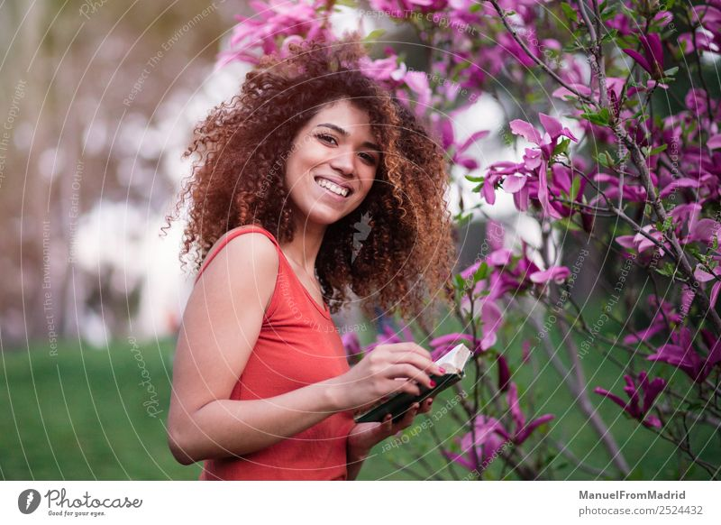 cheerful afro woman holding a book Lifestyle Happy Beautiful Leisure and hobbies Reading Summer Garden School Study Camera Human being Woman Adults Book Nature