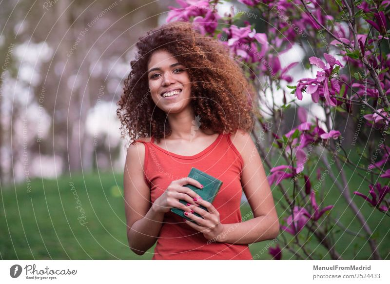 cheerful afro woman holding a book Woman Human being Nature Summer Beautiful Tree Flower Black Lifestyle Adults Happy Grass Garden School Leisure and hobbies