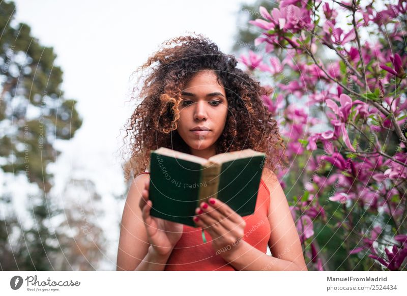 afro woman reading a book outdoors Lifestyle Happy Beautiful Leisure and hobbies Reading Summer Garden School Study Human being Woman Adults Book Nature Tree