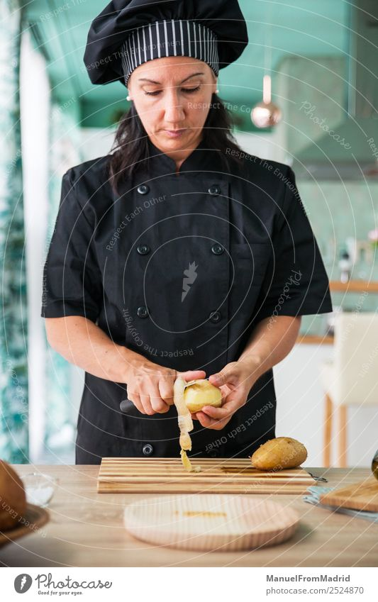 woman chef peeling a potato Nutrition Plate Table Kitchen Human being Woman Adults Hand Wood Modern Concentrate cook potatos Potatoes food Professional knife