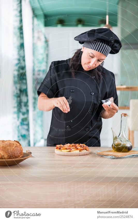 woman chef seasoning a dish Herbs and spices Nutrition Plate Table Kitchen Human being Woman Adults Hand Hat Wood Modern cook adding salt Octopus galician pulpo