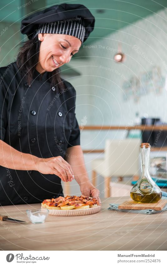 woman chef seasoning a dish Herbs and spices Nutrition Plate Happy Table Kitchen Human being Woman Adults Hand Hat Wood Smiling Modern cook adding salt Octopus