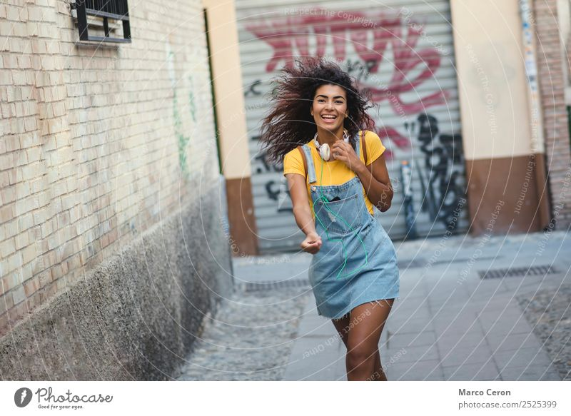 beautiful african girl casual dressed with headphones walking happy in the street listening music backpack black blue brown hair celular colours curly hair cute