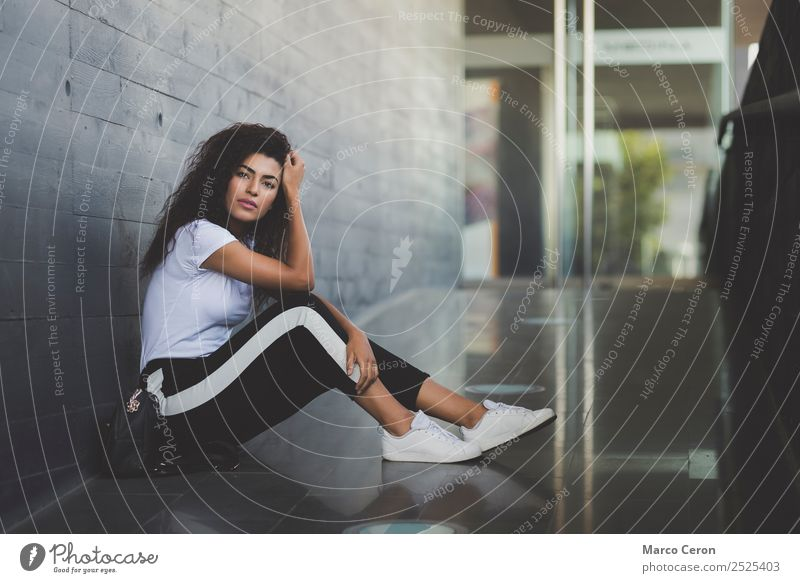 beautiful young woman sitting on the floor in introspective pose. Attractive mixed race girl casual dressed sitting on the street thnking about her dreams.t