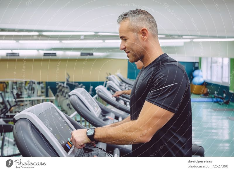 Man setting control panel of treadmill for training Lifestyle Leisure and hobbies Sports Jogging Technology Human being Adults Hand Observe Touch Movement