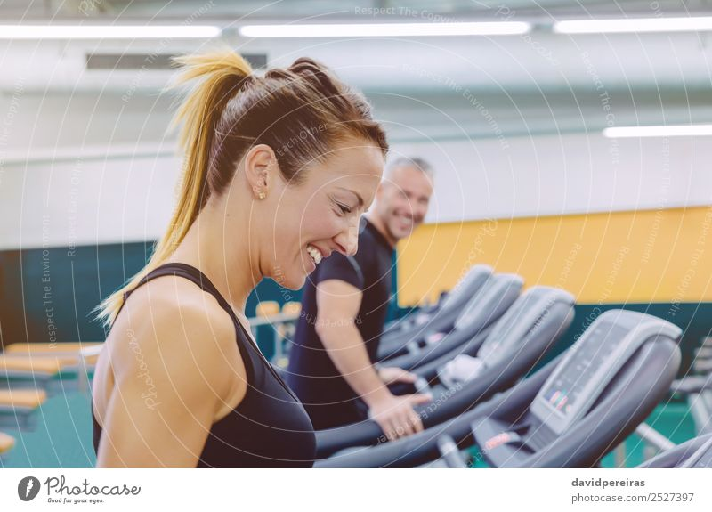 Fitness woman laughing with friend in treadmill training Lifestyle Joy Happy Beautiful Face Leisure and hobbies Sports Jogging Human being Woman Adults Man