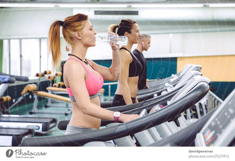 Woman drinking water while training on treadmill Drinking Bottle Lifestyle Beautiful Leisure and hobbies Music Sports Jogging Human being Adults Man Fitness