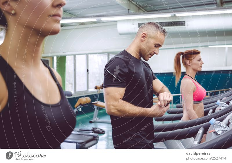 Man checking heart rate on watch in treadmill training Lifestyle Sports Jogging Screen Technology Human being Woman Adults Heart Observe Fitness Authentic Smart
