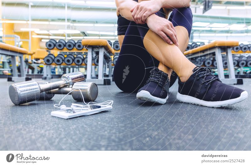 Sporty woman sitting with dumbbells and smartphone in gym floor Lifestyle Beautiful Body Leisure and hobbies Music Sports Telephone PDA Human being Woman Adults