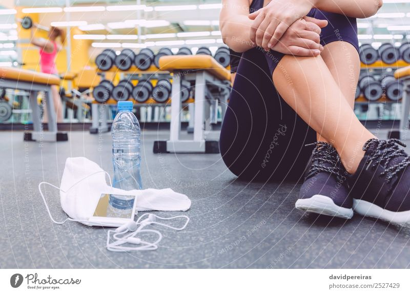 Sporty woman sitting with dumbbells, water and smartphone in gym Bottle Lifestyle Beautiful Body Leisure and hobbies Music Sports Telephone PDA Human being