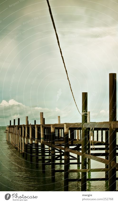 Connection to the top: a wooden footbridge into the sea with a rope to the top Environment Nature Water Sky Clouds Storm clouds Horizon Weather Waves Beach
