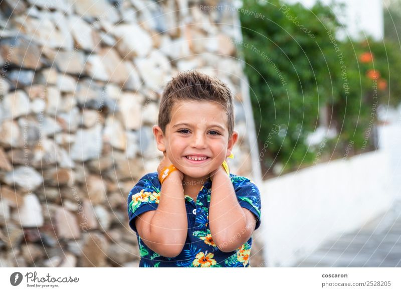 Portrait of a cute little boy against of a stone wall Child Human being Man Summer Blue Beautiful White Flower Face Adults Style Happy Boy (child) Small Fashion