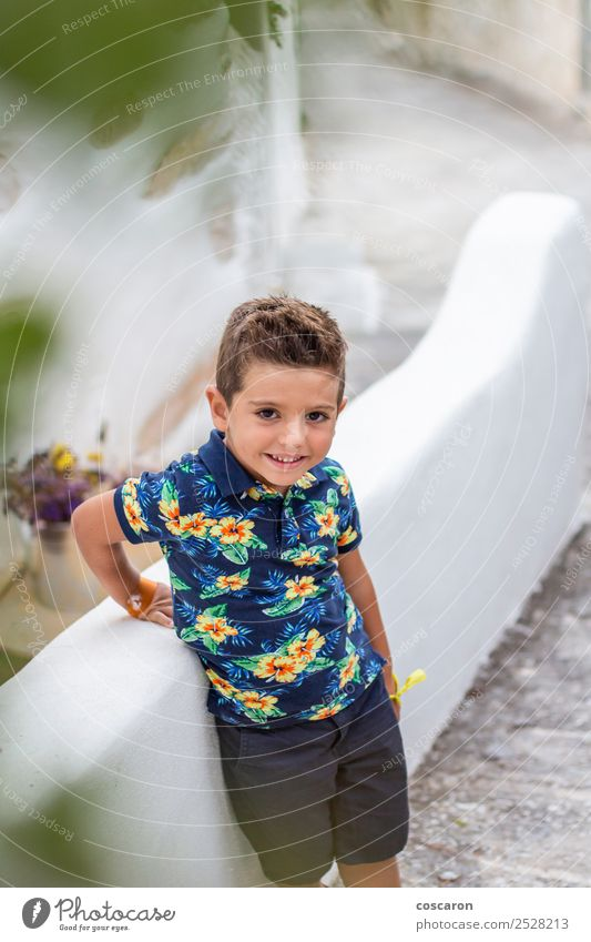 Portrait of a cute little boy against of a stone wall Child Human being Man Summer Blue Beautiful White Flower Face Adults Happy Style Boy (child) Small Fashion