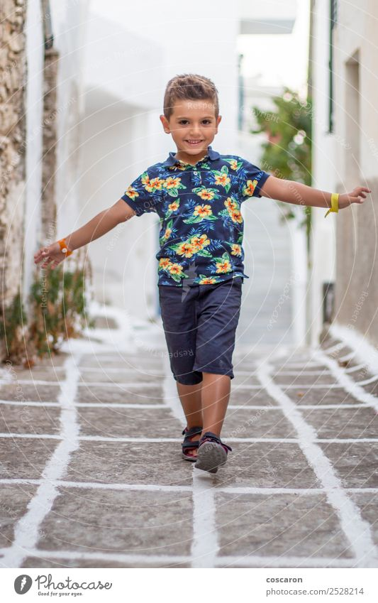 Little cute child doing balance on the street of a Greek village Child Human being Vacation & Travel Man Beautiful White Flower Joy Street Adults Lifestyle
