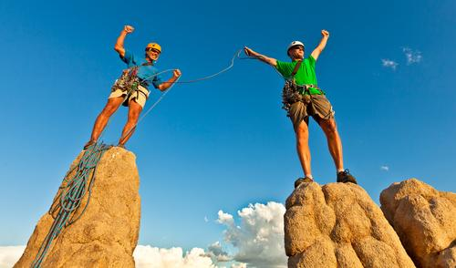 Rock climbing team standing on the summit. Human being Man Adults Sports Power Rope Success Climbing Trust Peak Brave Athletic Balance Top Teamwork Willpower