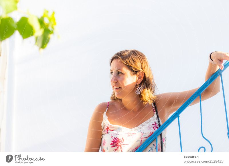 Middle aged woman leaning on a blue railing in a greek village. Woman Human being Sky Vacation & Travel Summer Plant Beautiful White Ocean Eroticism Black