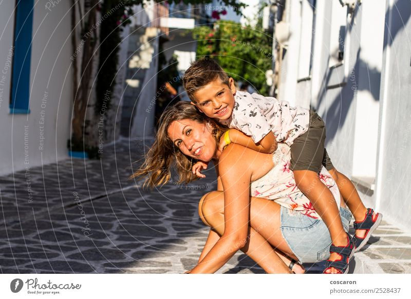 Boy climbed on his mother's back on the street of a Greek village Lifestyle Joy Happy Beautiful Playing Vacation & Travel Tourism Summer Island Child