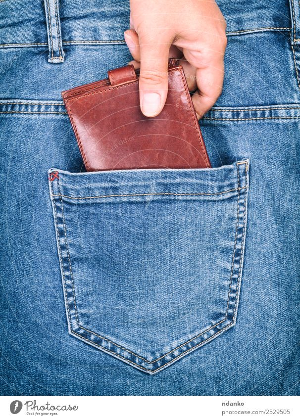 female hand clings to a purse Style Money Business Human being Woman Adults Hand Fashion Clothing Pants Jeans Leather To hold on Blue Brown Crisis Risk Lose
