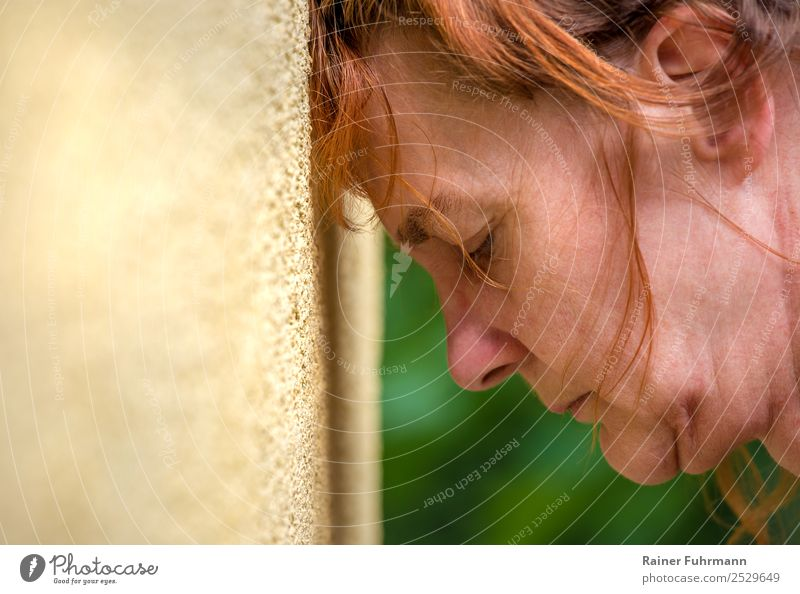 a woman leans her head against a wall Human being Feminine Woman Adults Female senior Head 1 Red-haired Sadness Old Emotions Moody Fatigue Pain Longing