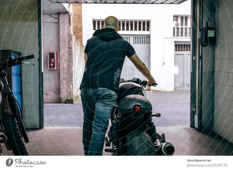 Man with custom motorbike leaving the garage Lifestyle Style Vacation & Travel Trip Engines Human being Adults Street Motorcycle Jeans Bald or shaved head Stand