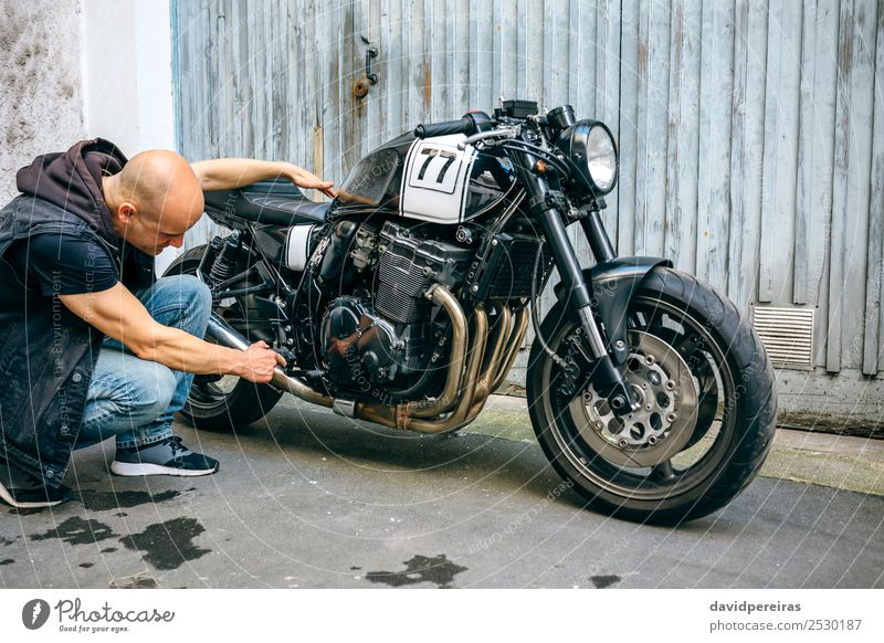 Biker checking with a motorcycle Lifestyle Style Trip Engines Human being Man Adults Street Vehicle Motorcycle Sneakers Bald or shaved head Authentic Retro