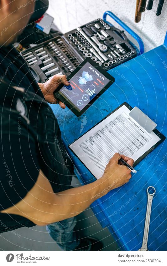 Mechanic using tablet app and taking notes Human being Man Adults Work and employment Decoration Checkered Motorcycle Vertical Guy Tablet computer Repair