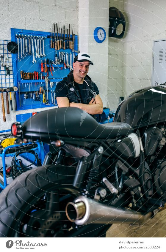 Mechanic posing with a motorcycle Lifestyle Style Happy Work and employment Engines Human being Man Adults Vehicle Motorcycle Smiling Authentic Retro Black