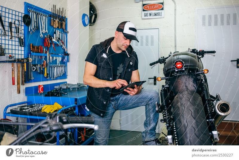 Mechanic checking custom motorcycle with tablet Lifestyle Style Work and employment Engines Technology Human being Man Adults Vehicle Motorcycle Authentic