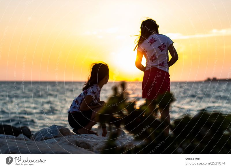 Two girls on the breakeater at sunset Lifestyle Joy Happy Beautiful Relaxation Vacation & Travel Camping Summer Sun Beach Ocean Child Boy (child)