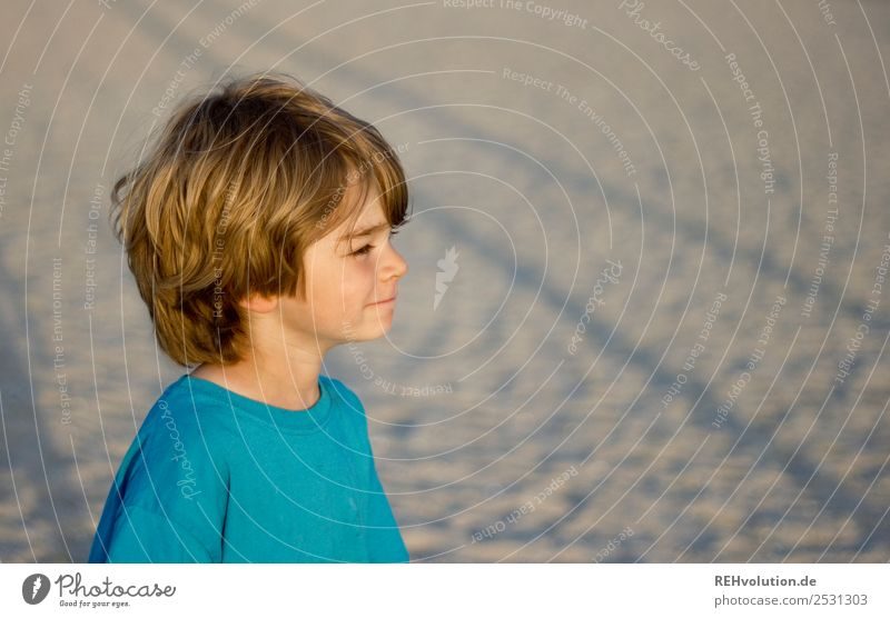 Child standing on the beach Upper body portrait Shallow depth of field Sand naturally Authentic Observe Nature Environment Sun Beach Summer vacation Trip