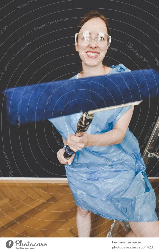 Woman in protective clothes posing with a blue paint roller #DIY Leisure and hobbies Feminine Adults 1 Human being 18 - 30 years Youth (Young adults)