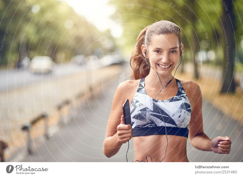 Fit healthy athletic woman jogging on a river bank Lifestyle Summer Music Sports Jogging PDA Woman Adults Warmth Park Street Fitness Smiling running Practice