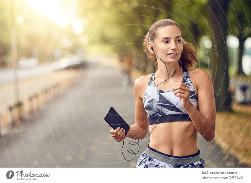 Fit healthy athletic woman jogging on a river bank Lifestyle Summer Music Sports Jogging PDA Woman Adults 1 Human being 18 - 30 years Youth (Young adults)