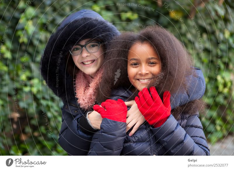 Two happy girls in the park with coats Joy Happy Beautiful Face Winter Child Human being Family & Relations Friendship Infancy Park Coat Scarf Gloves Afro