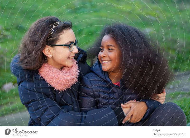 Two happy girls in the park with coats Joy Happy Beautiful Face Winter Child Human being Family & Relations Friendship Infancy Grass Park Coat Scarf Gloves Afro
