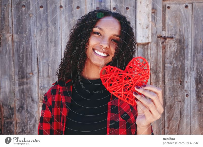 Beautiful and happy young woman holding a heart Human being Youth (Young adults) Young woman Red Joy 18 - 30 years Black Lifestyle Adults Healthy Love Feminine