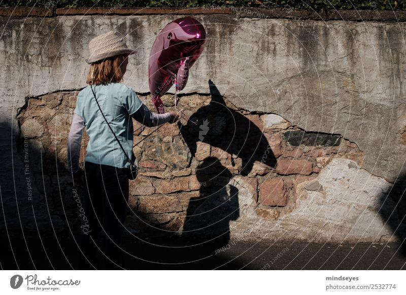 Girl with a dolphin balloon casts a shadow on the wall Playing Fairs & Carnivals Human being Feminine Infancy 1 Wall (barrier) Wall (building) Hat Dolphin Toys