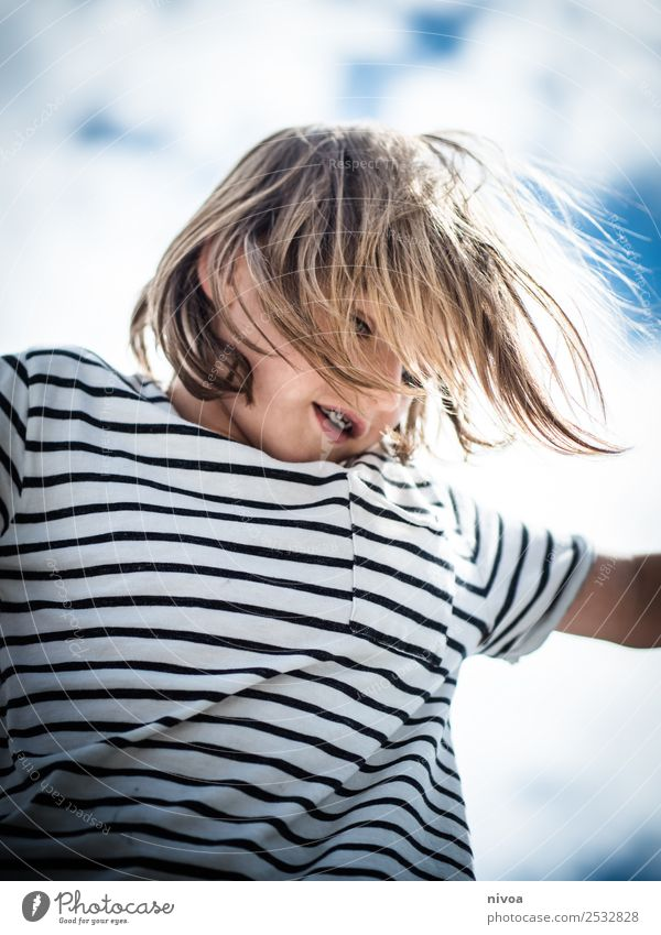 Blond boy plays with blowing hair Joy Happy Parenting Child Human being Masculine Boy (child) 1 8 - 13 years Infancy Environment Clouds Sun Beautiful weather