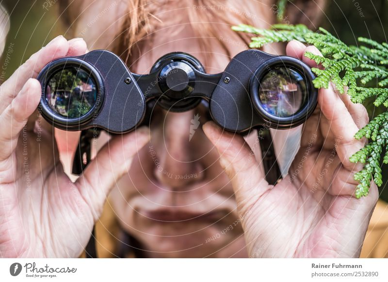 a woman looks through binoculars Human being Feminine Woman Adults 1 Spring Summer Beautiful weather Red-haired Binoculars Observe Curiosity Jealousy Envy