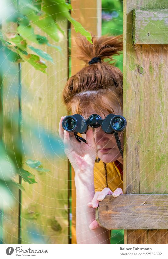 "a curious woman observes with binoculars Human being Feminine Woman Adults Head 1 Environment Garden Fence Observe Curiosity Watchfulness Envy ""Binoculars"