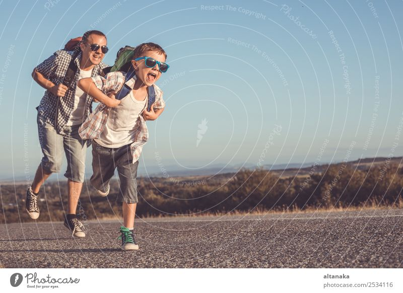 Father and son running on the road at the day time. Concept of tourism. Lifestyle Joy Happy Leisure and hobbies Vacation & Travel Tourism Trip Adventure Freedom