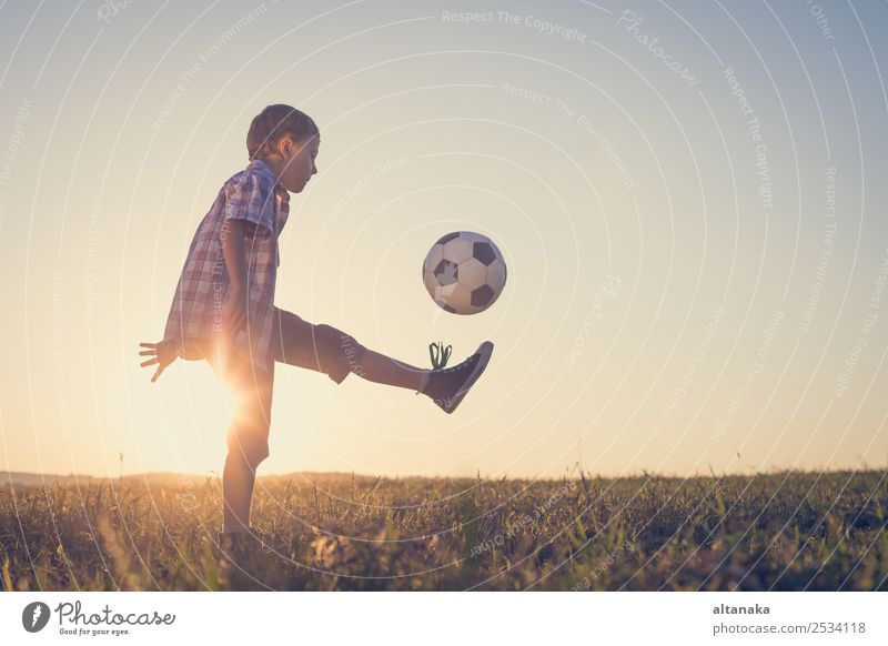 Young little boy playing in the field with soccer ball. Concept of sport. Lifestyle Joy Happy Relaxation Leisure and hobbies Playing Summer Sports Soccer Child