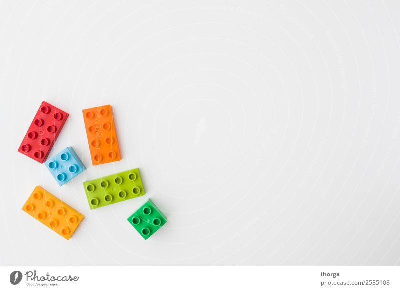 toy bricks of assorted colors on white background Design Joy Leisure and hobbies Playing Entertainment Child Infancy Building Toys Brick Plastic Blue Yellow