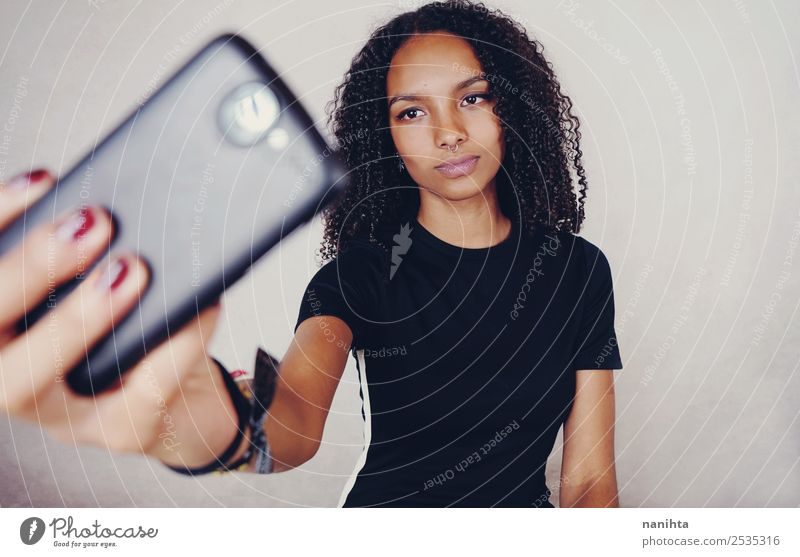 Young woman taking a selfie with her phone Lifestyle Style Design Beautiful Hair and hairstyles Skin Face Cellphone Camera PDA Technology
